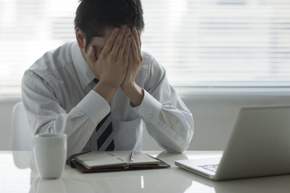 załamany mężczyzna siedzący przy biurku